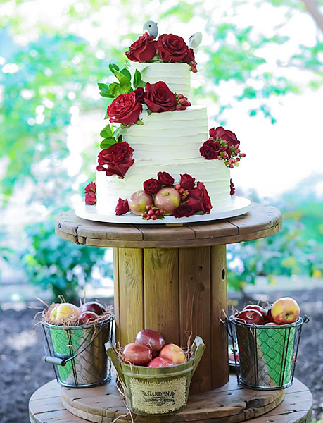 Wedding cake with fresh flowers and apples